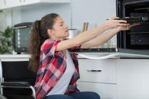 Mädchen im Rollstuhl schiebt Blech in den Ofen