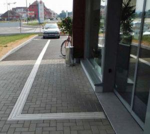 Barrierefreies bauen nach DIN 18040: Bodenleitsystem vom Behindertenparkplatz zum Eingang eines Ladengechäftes