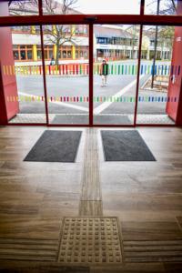 Eingang: Glastüre mit bunten Markierungen und taktile Bodenelemente
