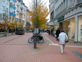Verkehrsraum: Fußgängerzone in Gießen mit deutlich unterschiedenen Bereichen. Die Möblierung steht in der Zone mit dunklem Natursteinpflaster, ein Leitstreifen führt an den Geschäftsauslagen vorbei, und in der breiten Mittelzone bietet eine Muldenrinne zusätzliche Orientierung.