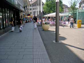 Der umlaufende Flanierbereich des Platzes in Gießen ist mit großen Platten ausgelegt und durch einen Leitstreifen begrenzt. Optisch wahrnehmbar ist die Materialgrenze zum Platzinneren, wo sich alle Einbauten und die Gastronomie befinden.