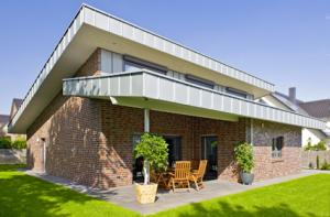 Die Fenstertür aus der Küche und das Schiebefenster des Wohnraums führen schwellenlos auf die Terrasse, die sich auf der Südseite des Bungalows befindet – unterhalb des zehn Grad geneigten Gründaches.