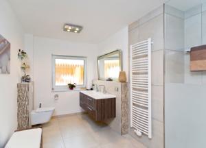 Das Bad ist knapp 13 Quadratmeter groß. Der Fliesenbelag findet sich im gesamten Geschoss wieder. Zugunsten einer großen bodengleichen Dusche mit feststehendem Glaselement wurde auf eine Badewanne verzichtet. Ein Doppelwaschtisch sorgt am Morgen für notwendige Entspannung.